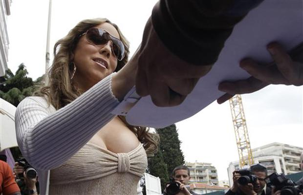 ** ALTERNATIVE CROP ** U.S. singer Mariah Carey signs an autograph for a fan as she arrives for a photo call during the 62nd International film festival in Cannes, southern France, Friday, May 15, 2009. (AP Photo/David Azia)