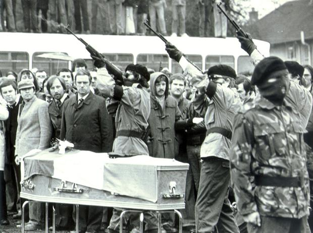 Masked gunmen fire a volley of shots beside hunger striker Bobby Sands coffin, at Milltown Cemetery.