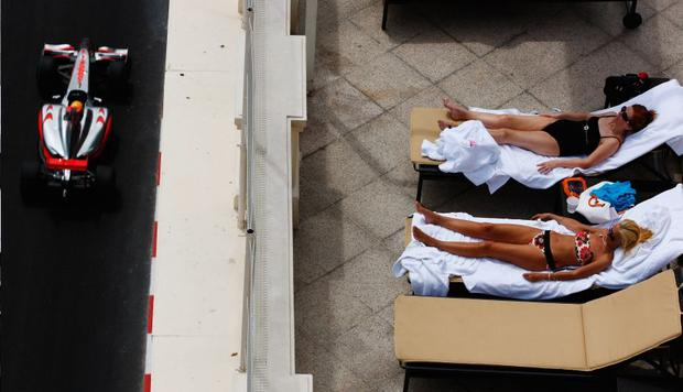 Some spectators enjoy the sun as Lewis Hamilton blasts past on his way to the quickest time in Monaco yesterday