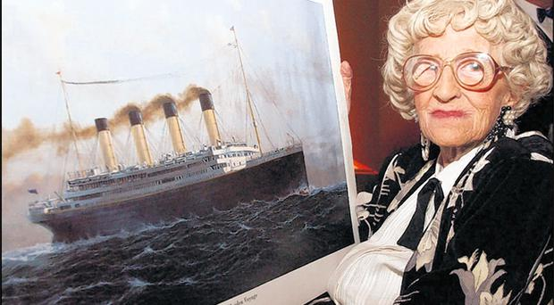 Titanic disaster survivor Millvina Dean with a picture of the stricken vessel