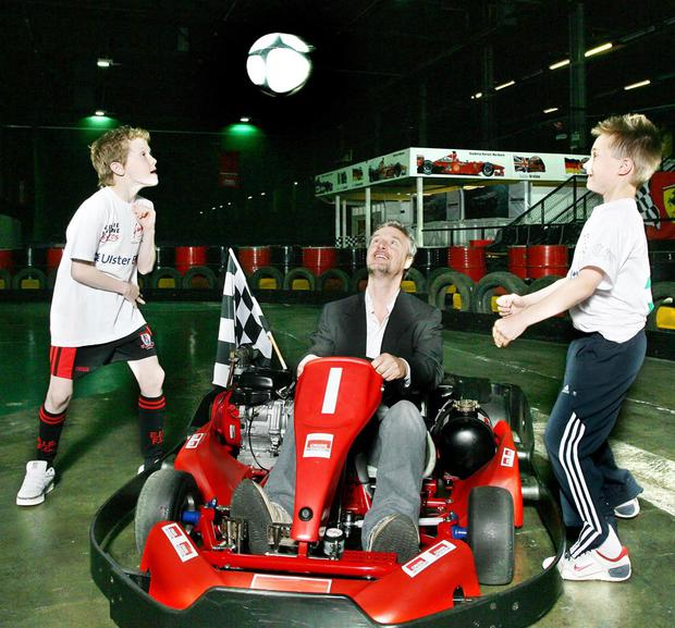 Eddie Irvine with young footballers Jack Watson (left) and Alexander McIlmain, whose grandfathers played with George Best