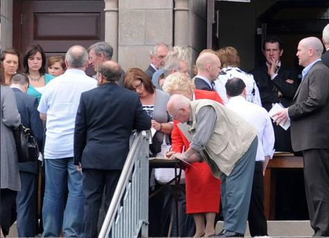 Family and friends sign the book of condolence at the memorial service for Eithne Walls