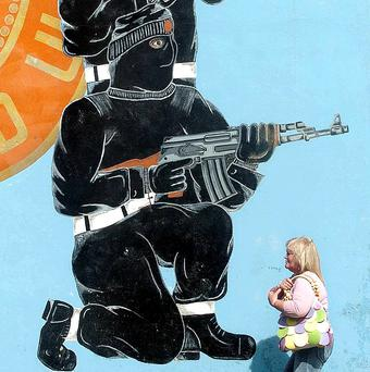 Writing on the wall for weapons: A woman walks past a loyalist paramilitary mural in Belfast
