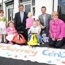 Denis Rooney of the IFI (left), Paul Roberts of Ashton Community Trust and DSD Minister Margaret Ritchie are joined by local children at the opening of the new business centre