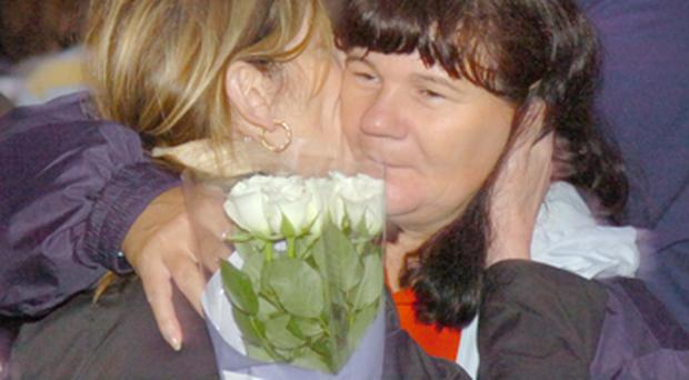 Pauline Holland (left) embraces a friend at the vigil for her husband Harry