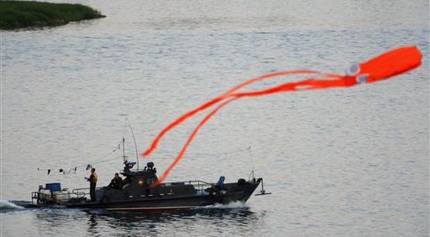 A North Korean patrol boat is seen near a large octopus shaped kite along the Yalu river near Dandong, China, Tuesday, June 2 , 2009. North Korea pushed forward with preparations to test-fire more missiles in the wake of last week's nuclear test as leader Kim Jong Il moved to anoint his third son as heir to the world's first communist dynasty, reports and experts said Tuesday. (AP Photo/Ng Han Guan)
