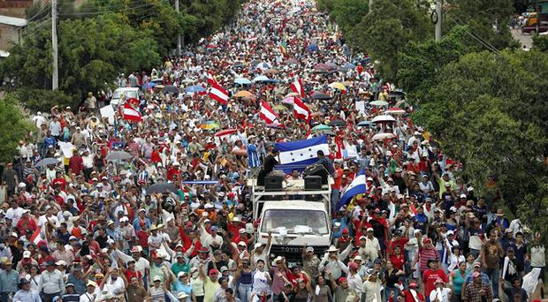 Thousands of supporters of ousted President Manuel Zelaya march towards the international airport