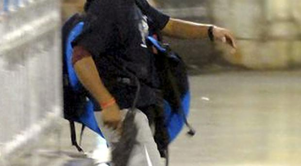 A gunman walks at the Chatrapathi Sivaji Terminal railway station in Mumbai, India, Wednesday, Nov. 26, 2008.