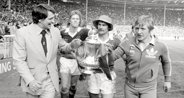 former England manager Sir Bobby Robson - seen as Ipswich Town manager (left) with coach Cyril Lea and players David Geddis and captain Mick Mills (hat) as they parade the FA Cup in triumph at Wembley Stadium in London