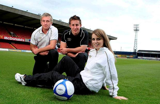 Linfield footballers Mark McAllister and Rober Garrett pose with model Lucy Evangelista