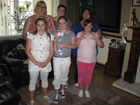 Margaret Hall (top left) and Debbie Neely (top right) with four of the five children of their travelling party holding the photographic Electoral Identity Card that is not considered valid ID by the airline Ryanair