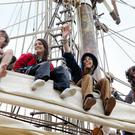 Young people from Canada get their first glimpse of Belfast from the yardarm of the Tall Ship Europa