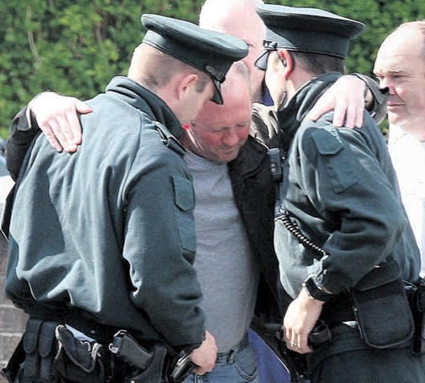 Clive Elliott is comforted by police after visiting the place where his son James disappeared