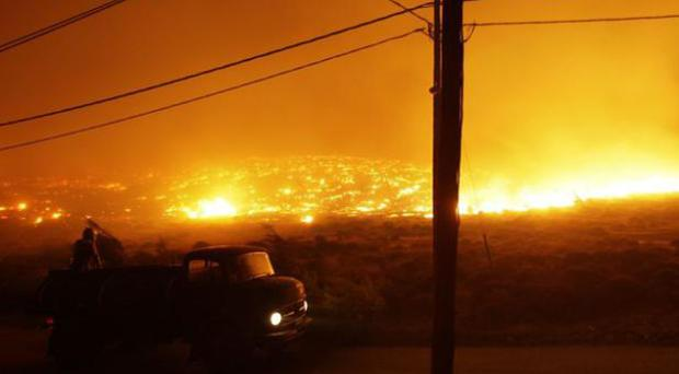 A man watches the wildfires spread across Mount Penteli, Athens, yesterday