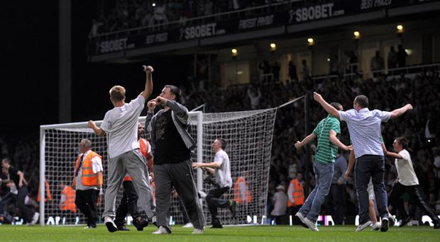Fans invade the pitch during the Carling Cup second round match between West Ham United and Millwall at Upton Park