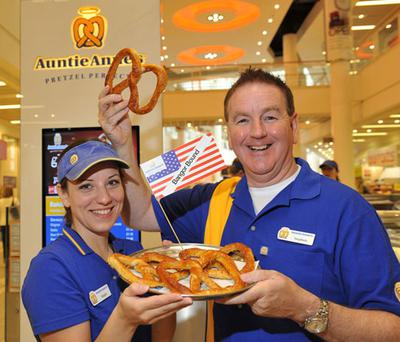 Stephen Downey, master franchisee of Auntie Anne's Pretzels, with Magda Serb, Pretzel baker