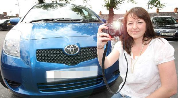 Hi-tech makeover: East Belfast woman Katrina Martin takes a picture of her car to put up for sale