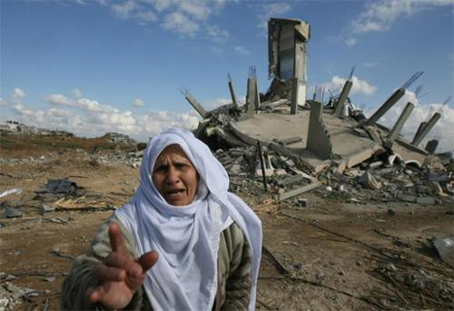 A Palestinian woman next to her home destroyed during Israeli strikes in Jabalia refugee camp in the Gaza Strip in January
