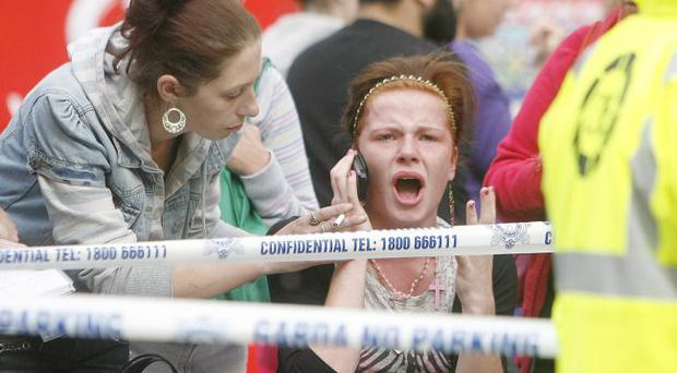 A woman reacts at the scene of a crash between a Bus and a Luas tram on Dublin's O'Connell Street.