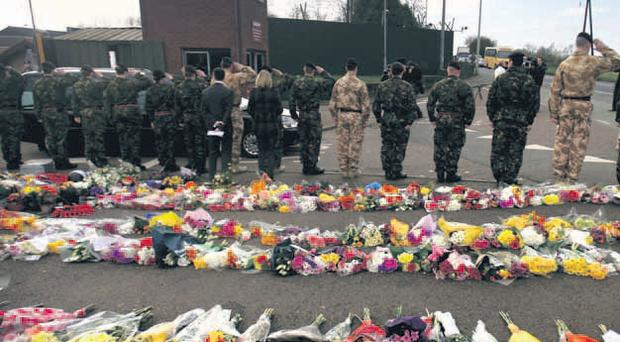 Comrades stand amid massed floral tributes as they salute murdered Sappers Patrick Azimkar and Mark Quinsey as their bodies were borne away from Massereene Barracks in March