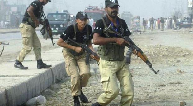 Pakistani police commandos rush to a police training school in Lahore after yesterday's attack