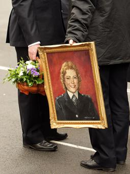 Police officers hold flowers and a portrait of Yvonne Fletcher prior to a ceremony to mark the 25th anniversary of the killing of WPC Yvonne Fletcher on April 17, 2009 in London, England. WPC Yvonne Fletcher, 25, was helping to control a small demonstration outside the Libyan embassy in St James's Square, London when she was killed by automatic gunfire on April 17, 1984.