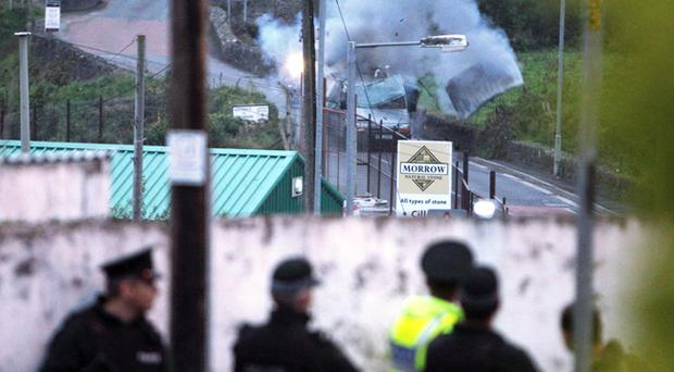 Police officers watch the controlled explosion