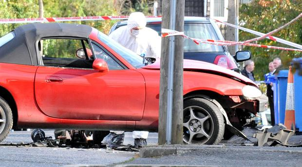 An army bomb disposal expert examines the scene of the explosion at Kingsdale Park near police HQ in east Belfast this morning (Picture by Alan Lewis - Photopress Belfast)