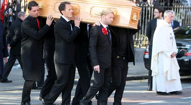 Ronan Keating, Keith Duffy, Mikey Graham and Shane Lynch carry out the coffin after the funeral of Boyzone singer Stephen Gately at St Laurence O'Toole Church in Dublin