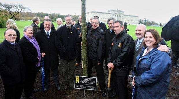 Sinn Fein President Gerry Adams (4th left) and Ulster GAA President Tom Daly (3rd right) who unveiled a plaque below the mature Ash tree planted at Stormont