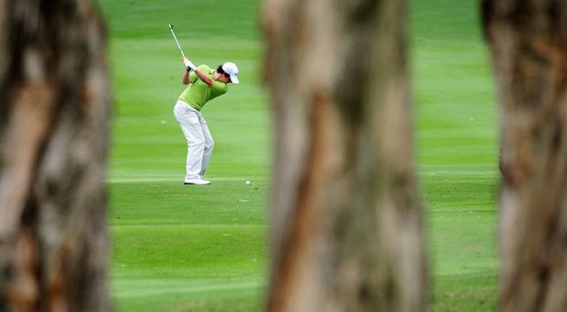 Rory McIlroy plays his approach shot on the 14th hole during the first round of the UBS Hong Kong Open at the Hong Kong Golf Club