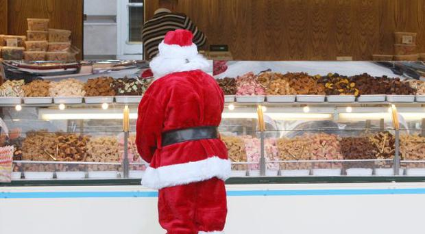 Santa Claus admires some of the continetal on sale as traders from all over Europe and much further afield open the Christmas Continental Market at City Hall in Belfast