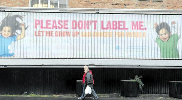 A passer-by walks past the giant humanist poster in Belfast city centre yesterday