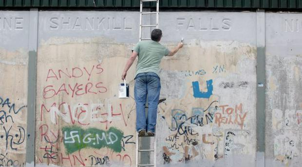Artists work on the Peace wall in west Belfast, which separates the Shankill (Protestant) from the Falls Road (Catholic) area of the city.