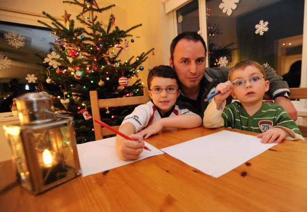 Press Eye Belfast - Northern Ireland - 28th November 2009 Hospice Christmas stars.Paul Watson and sons Mark and Euan prepare letters to Santa Picture by Stephen Hamilton / Press Eye.