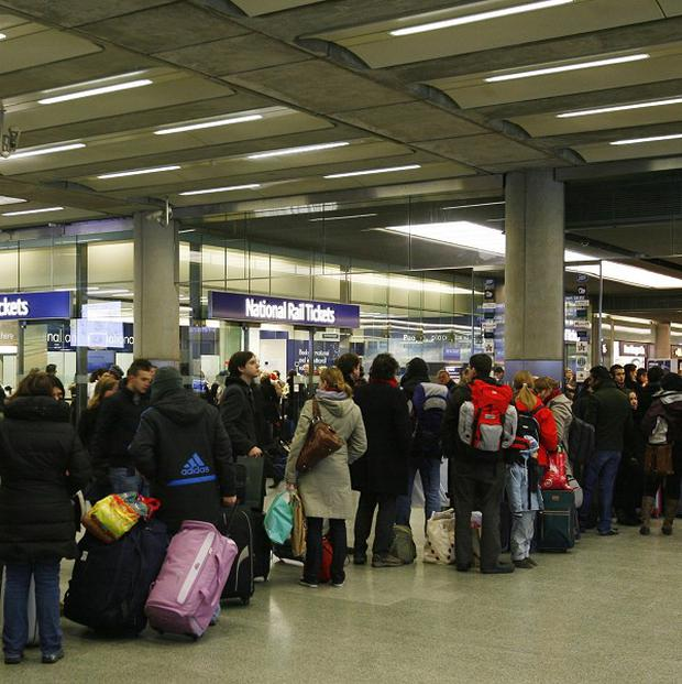 Passengers queue outside a National Rail office at St Pancras
