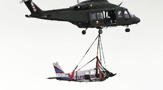 An Irish Army helicopter removes the plane wreckage following the crash