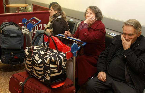 Passengers wait for flights