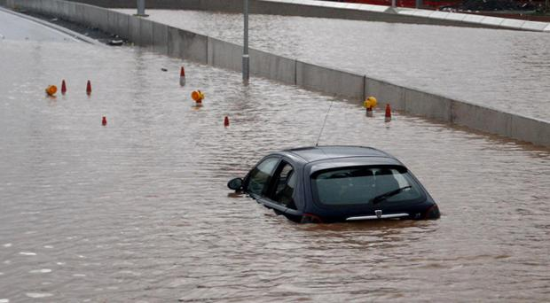 A motorist is caught in the severe floods on the Westlink area of Belfast.
