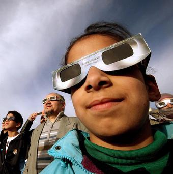 Residents watch a solar eclipse in Amman, Jordan