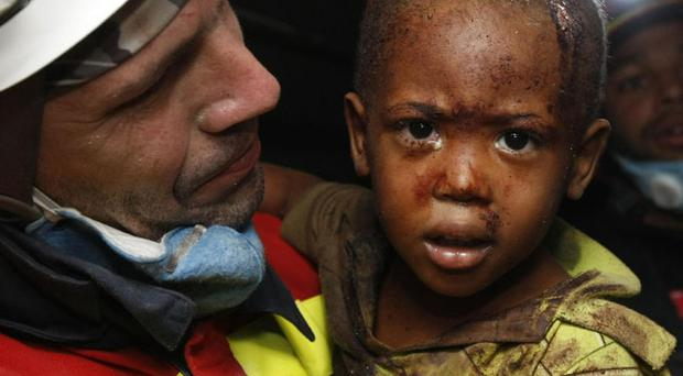 Spanish rescuer carries two-year-old Redjeson Hausteen Claude after he was rescued from a collapsed home