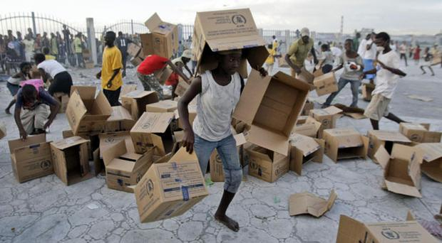 Youths collect empty boxes after a food distribution by the UN near Cite Soleil in Port-au-Prince, Saturday, Jan. 16, 2010.