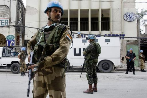 An Indian FPU officer secures the perimeter of a bank in conjunction with Brazilian UN peacekeepers January 19, 2010 in downtown Port-au-Prince, Haiti