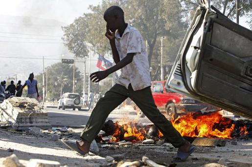 A Haitian walks past a burning corpse in the street in the aftermath of the massive Jan. 12 earthquake in Port-au-Prince, Monday, Jan. 25, 2010. Some Haitians have been burning bodies to eliminate the stench.(AP Photo/Gerald Herbert)