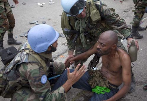 A United Nations soldier from Uruguay speaks to a man who was injured during a food distribution in Port-au-Prince, Monday, Jan. 25, 2010. People waiting in line for food began to loot the aid supplies in front of the National Palace, as a United Nations security force of Uruguayans tried to stop them. (AP Photo/Ramon Espinosa)