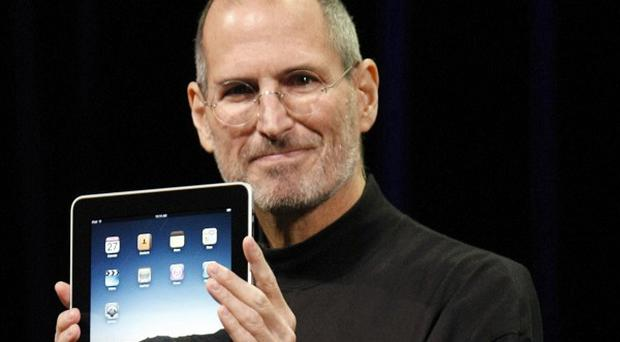 Apple CEO Steve Jobs shows off the new iPad during an event in San Francisco