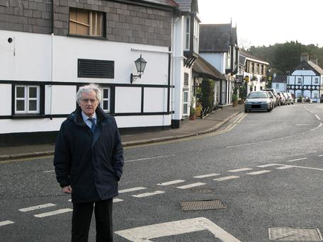 Alderman Brian Wilson at the junction of Ballymullan Road and Main Street with the Old Inn behind him
