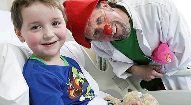 Ethan Martin (5), a patient at the Ulster Hospital in Dundonald, has a laugh with 'ClownDoctor' Paul Taylor, aka 'Dr Clooless'