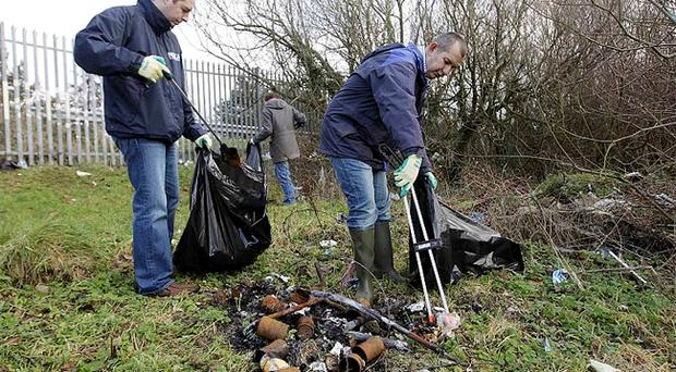 Lisburn councillor Paul Givan and Environment Minister Edwin Poots help with the clean-up off the Stewartstown Road on the outskirts of west Belfast