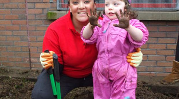 Young Naoimi Dunne helps Prince's Trust member Courtney Officer tidy the Victoria Day Centre Garden